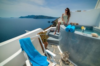 Luxurious Santorini hotel Kima Villas Oia woman enjoys the view of the sea and the Caldera from the balcony