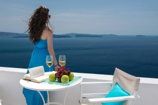 Luxurious Santorini hotel Kima Villas woman gazes at the Aegean Sea while relaxing in the balcony, drinking wine and tasting fresh fruits