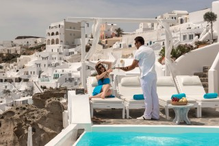 Luxurious Santorini hotel Kima Villas woman is offered a welcome drink in the balcony next to the jacuzzi