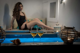 Luxurious Santorini hotel Kima Villas guest enjoying wine drinks in the heated jacuzzi