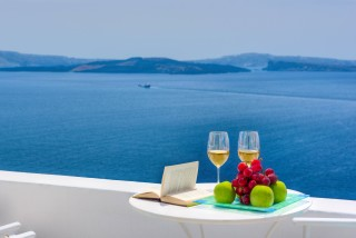 Luxurious Santorini hotel Kima Villas taste local wine and fresh fruits in the private balcony with sea view