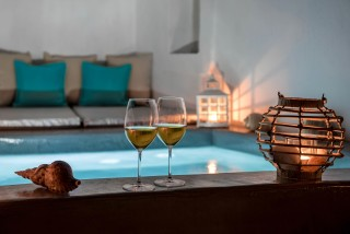 facilities of our santorini luxury hotel in oia kima villas jacuzzi and local wine by night