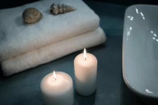 facilities of our santorini luxury hotel in oia kima villas towels and candles in the bathroom