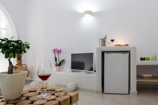 luxurious santorini suites kima villa with wine drinks, refrigerator, flat screen TV and flowers