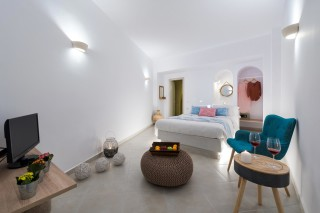 luxurious santorini suites kima villa deluxe double bedroom with welcome drinks, fresh fruits and flat TV screen
