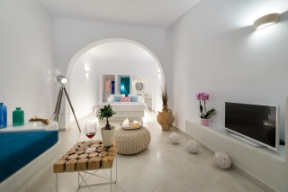 luxurious santorini suites kima villa big living room with sofa, flat TV screen and table right next to the cozy bedroom