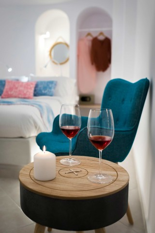 luxurious santorini suites kima villa enjoy a glass of wine as a welcome drink in the bedroom