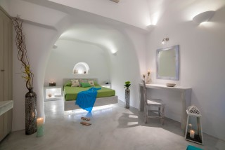 luxurious santorini superior cave suites kima villa bedroom next to the living room with A/C, flat screen TV, welcome drinks and lovely painting on the wall