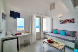 luxurious santorini superior suites kima villa sitting room with flat screen TV, A/C, big sofa and sea view